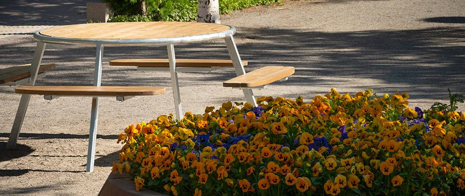 Referens/Projekt: Skellefteå Stadspark. PONGO bänkbord i utförande med stomme i varmförzinkat stål och sits/bordsskiva i Svanenmärkt ThermoWood® Furu. Runda bord med upp till 8 platser samt integrerad rullstolsplats. Smekab Citylife.